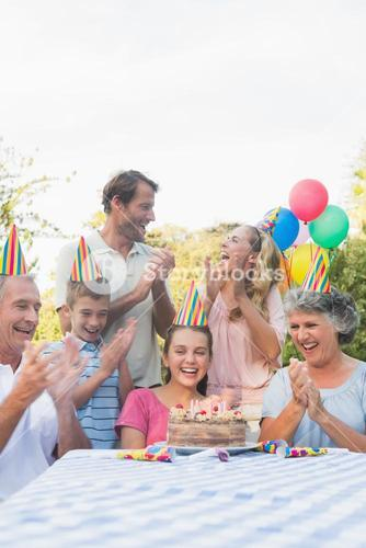 Cheerful extended family clapping for little girls birthday