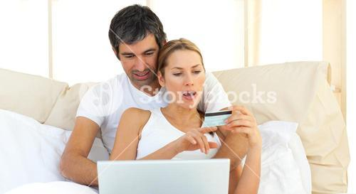 Loving couple using a laptop lying in the bed