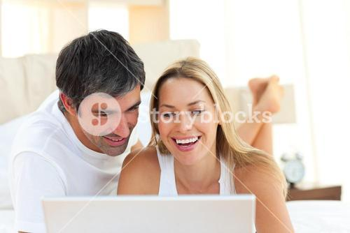 Close up of lovers using a laptop lying on bed