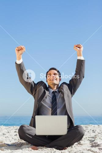 Victorious young businessman with his laptop