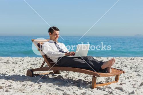 Young businessman lying on a deck chair with his laptop