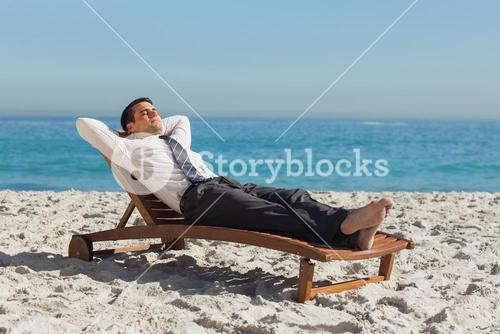 Young businessman relaxing on deck chair