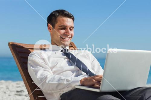 Happy young businessman on deck chair using his computer