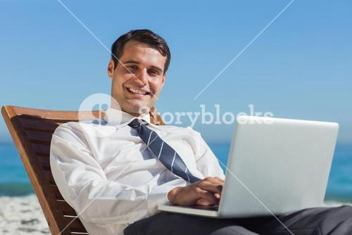 Cheerful young businessman lying on a deck chair with his computer