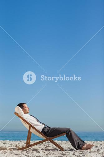 Young businessman relaxing and tanning on his deck chair