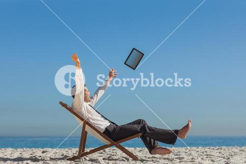 Victorious young businessman on his deck chair throwing his tablet away