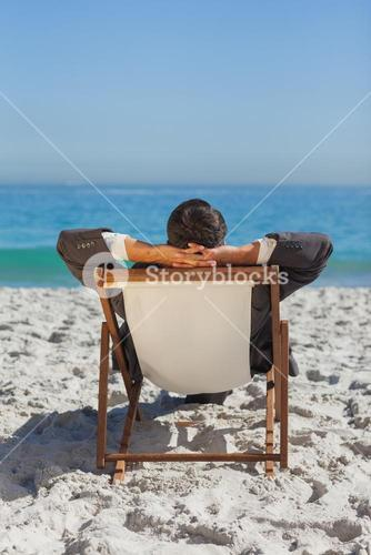 Relaxed young businessman resting on his sun lounger