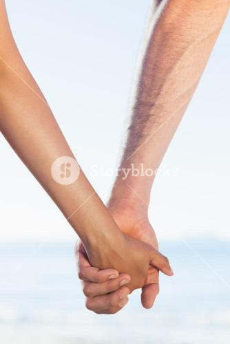Loving young couple grasping hands
