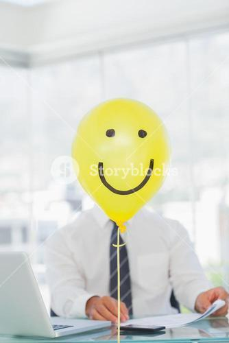 Yellow balloon with cheerful face hiding businessmans face