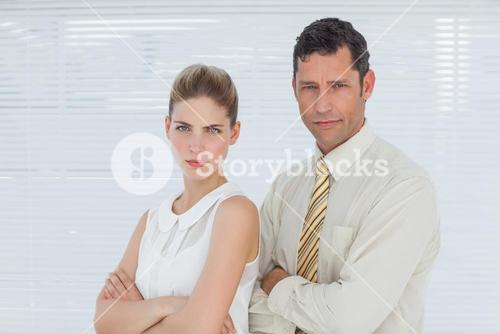 Frowning coworkers posing together