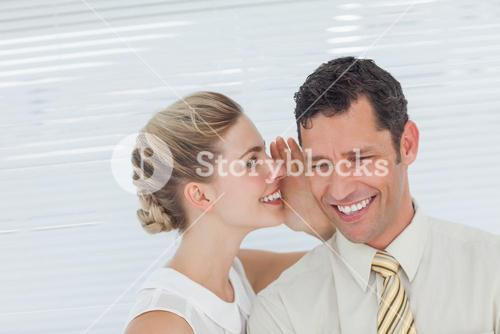 Businesswoman telling secret to her colleague