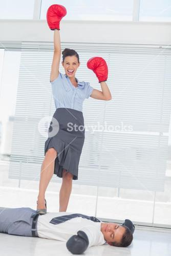 Businesswoman standing on defeated businessman wearing boxing gloves