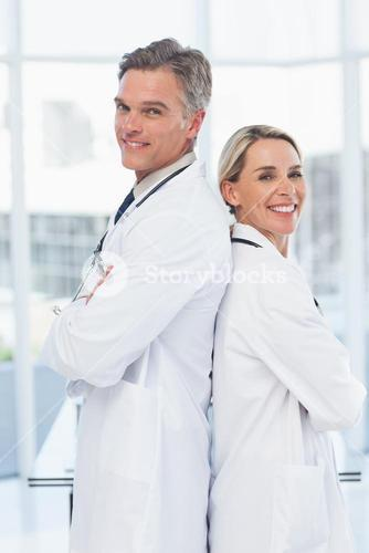 Experienced doctors posing together back-to-back
