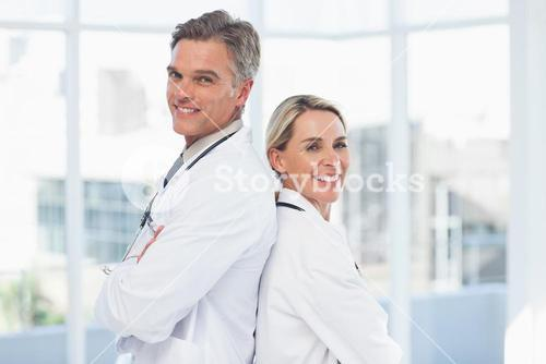 Smiling doctors posing together back-to-back