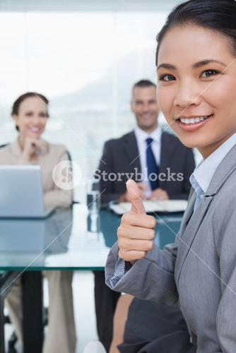 Young pretty applicant showing thumb up after obtaining the job