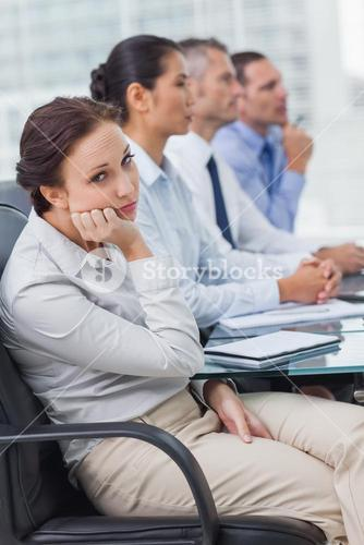 Bored businesswoman looking at camera while attending presentation