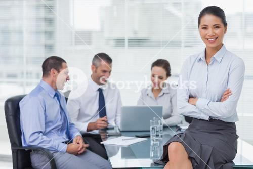 Smiling businesswoman posing while workmates talking together