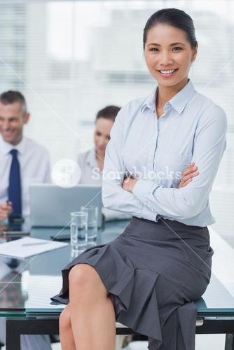 Smiling businesswoman posing with workmates on background