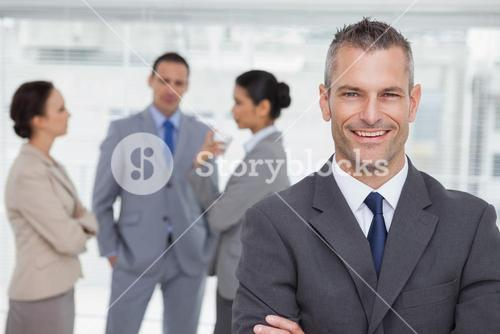 Smiling manager posing with employees in background