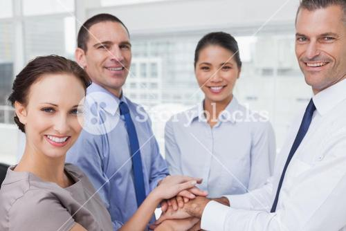 Cheerful work team joining hands together