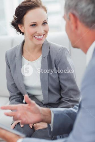 Smiling businesswoman listening to her workmate talking