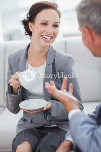 Cheerful businesswoman having coffee with her workmate