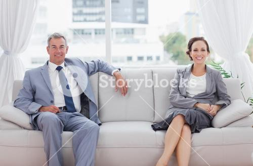 Workmates posing together sitting on sofa