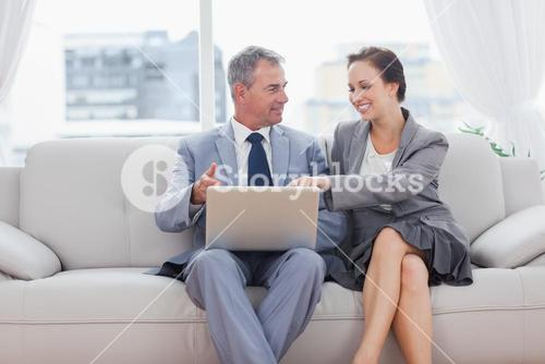 Cheerful workmates working together sitting on sofa