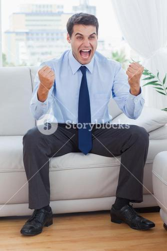 Victorious businessman cheering while sitting on sofa