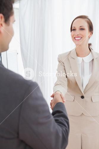 Cheerful businesswoman shaking hands with her new workmate