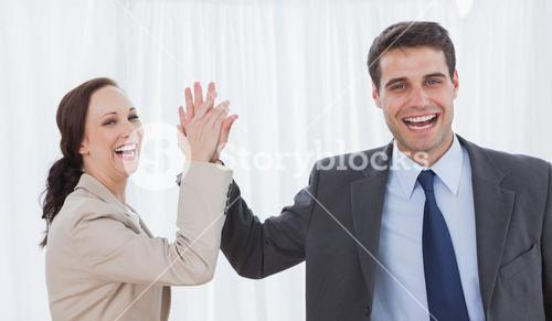 Cheerful workmates doing high five