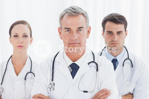 Serious doctors posing together crossing arms