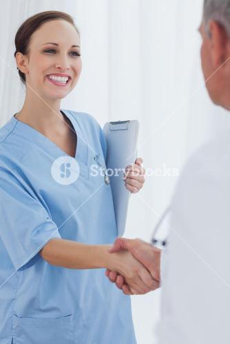 Cheerful pretty surgeon welcoming her new workmate