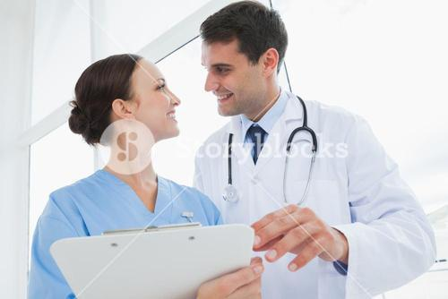 Cheerful doctor and surgeon looking at each other