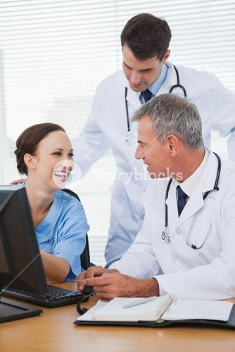 Surgeon working with doctors on computer