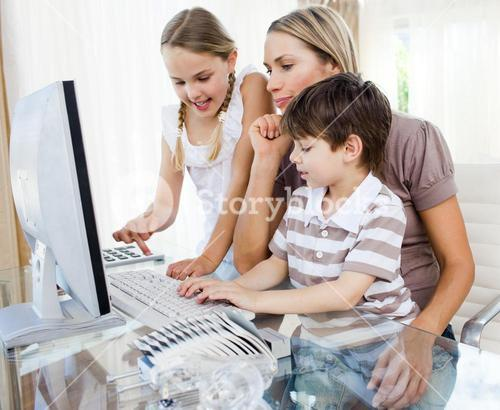 Attentive mother teaching her children how to use a computer