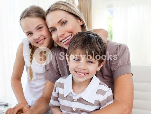 Attractive mother teaching her children how to use a computer