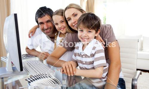 Portrait of a smiling family at a computer