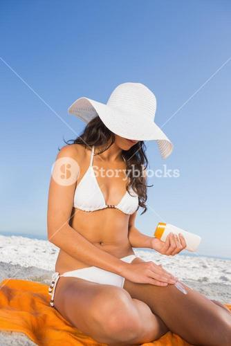 Sexy woman applying sun cream while sitting on her towel