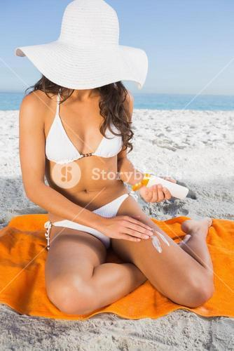Close up of young woman applying sun cream