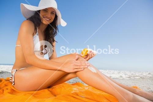 Cheerful young brunette with straw hat putting on sun cream