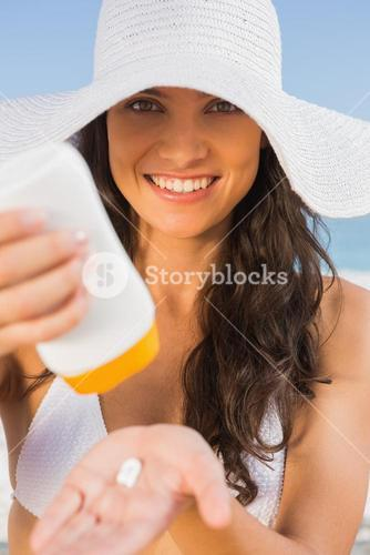 Smiling young brunette taking care of her body putting on sun cream