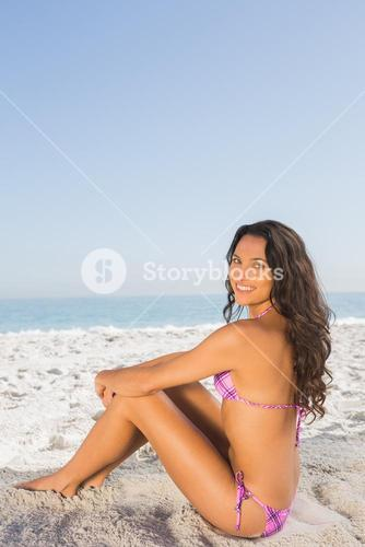 Cheerful sexy brown haired woman in pink bikini sitting