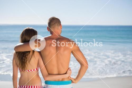 Loving couple embracing one another while looking at the sea
