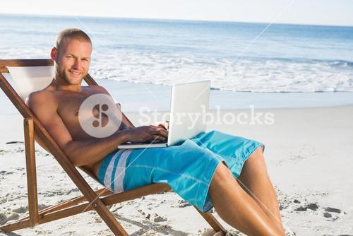 Smiling handsome man using his laptop while relaxing on his deck chair