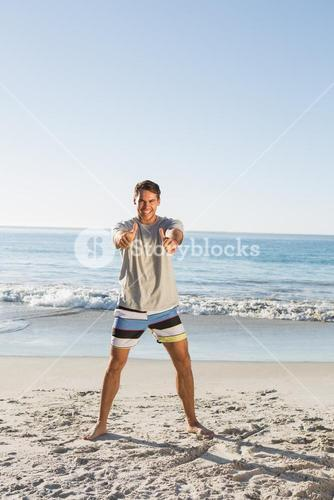 Energetic handsome man showing thumbs up to camera