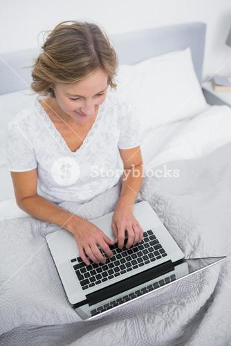 Content blonde woman in bed using her laptop
