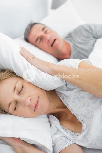 Tired wife blocking her ears from noise of husband snoring