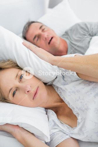 Tired wife blocking her ears from noise of husband snoring looking