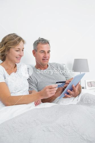 Relaxed couple using their tablet pc to buy online